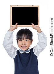 Asian Chinese little primary school girl holding chalkboard...