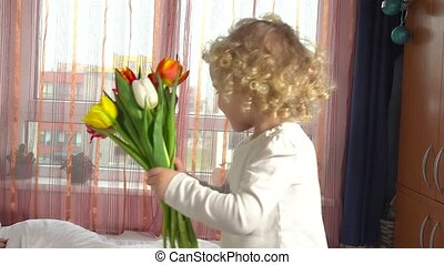 Cute little girl give flowers to happy mom and kiss on...