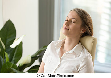 Calm attractive woman feeling relaxed leaning back on office...
