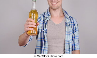Casual young man holding bottle of beer, smiling