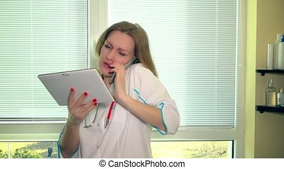 Doctor woman holding tablet computer while calling patient...