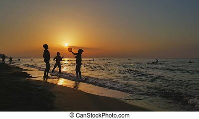 People playin ball on the beach at sunset