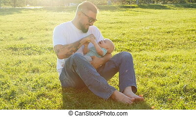 Father and little son on the grass in the park