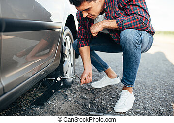 Man jack up broken car, wheel replacement. Vehicle with...