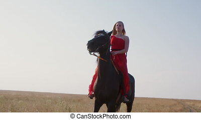 Young girl in long red dress riding black horse across a field