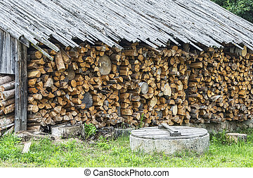 Under a canopy stacked firewood in a woodpile for the winter...