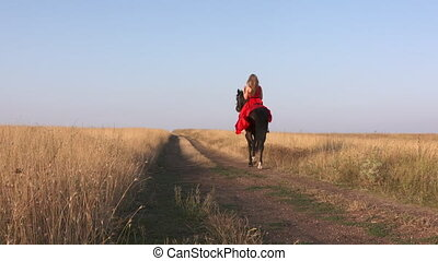 Young girl in long scarlet red dress riding black horse across dry grassland