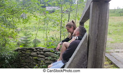 Young couple of tourists with backpacks siting on a bridge over a mountain river