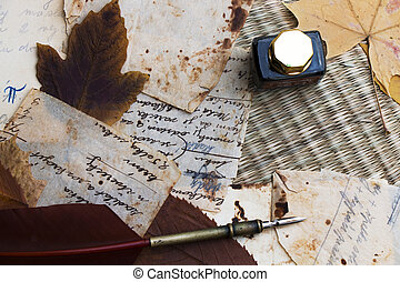 Still life. Old paper. Quill, ink and dry leaves on knitted straw. Recipe.