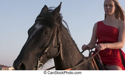 Young girl wearing long red dress riding black horse in...