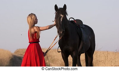 Young girl in long red dress leading saddled black horse in countryside