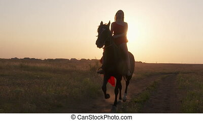 Young girl wearing long red dress riding black horse against...