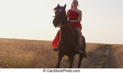 Female rider with her stallion walking on dirt road against clear sky in evening