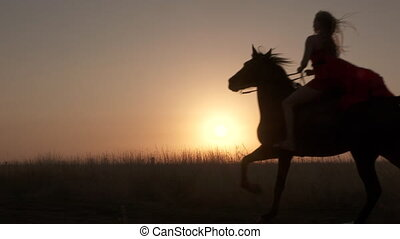 Silhouette of woman rider in red dress riding horse against the sun at sunset