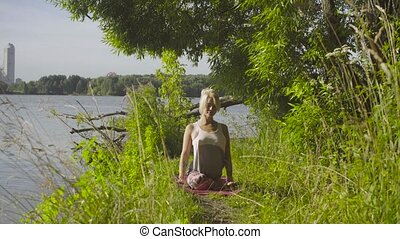 Woman doing yoga exercises on the river bank - Attractive...