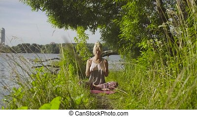 Woman doing breathing exercises - Attractive woman sitting...