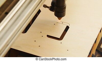 Laser torch cuts a wooden board or Plywood