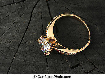 Jewelry ring with diamond on black wood background, copy-space