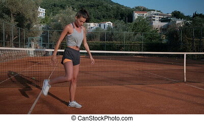 Slim woman flexing muscles on the outdoor tennis court....