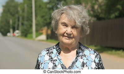 Portrait of serious old elderly woman outdoors