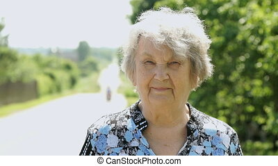 Portrait of smiling old woman aged 80s in the park next to...