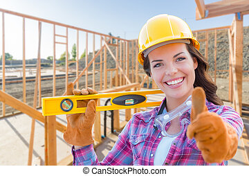 Female Construction Worker with Thumbs Up Holding Level...