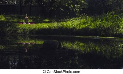 Young woman doing yoga asanas on the river bank - Attractive...