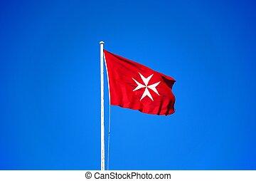 Maltese cross flag, Malta. - Maltese flag against a blue...
