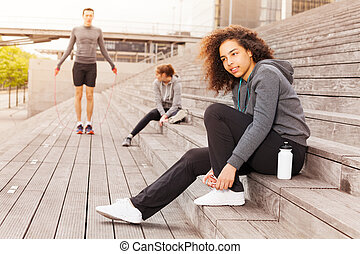African teenager in sportswear lacing her shoes - Side view...