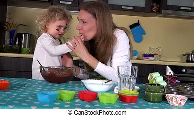 Crazy woman and little girl with chocolate dirty faces in kitchen