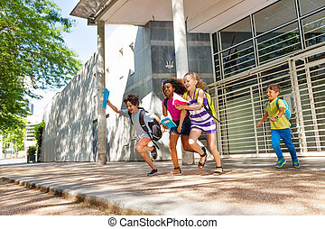 Group of kids run from the school