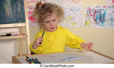 Emotional blonde girl child draw with pencil in book on...
