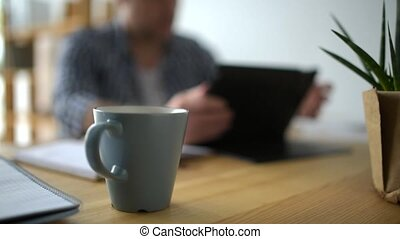 Dolly shot of a self employed man sitting on the table -...