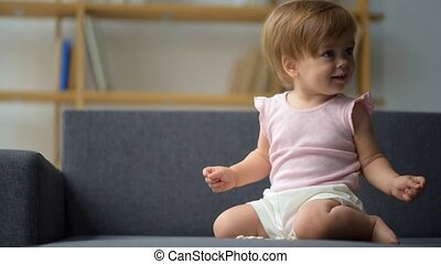 Nice little toddler sitting on the sofa - First stage of...