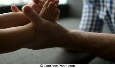 Close up of a caring father making a massage of a little...