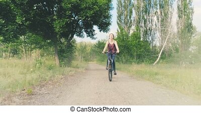 Girl rides a bicycle in the countryside - Young beautiful...