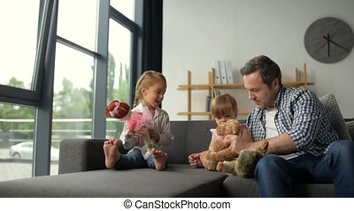 Positive caring father playing with his little daughters -...