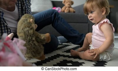 Curious pretty baby playing on the floor with her father -...
