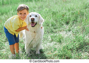 Cheerful boy hugging his dog on grass field