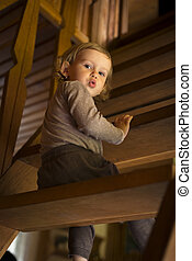 Surprised child sitting on wooden stairs in the cottage,...