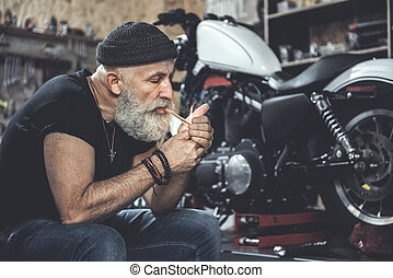 Busy old man smoking at workshop - Mature bearded biker is...