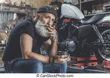 Sad old man smoking in workshop - Thoughtful mature bearded...