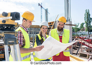 architect sharing ideas about plan of building project on construction site