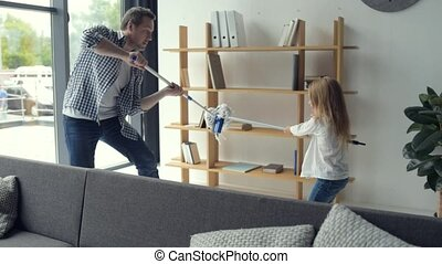 Cheerful father and daughter fighting with swabs - Real...