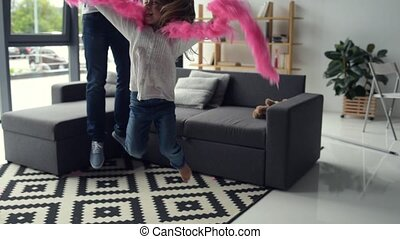 Cheerful girl and her father jumping at home - True...