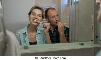 Man and woman in a bathroom brushing their teeth together....
