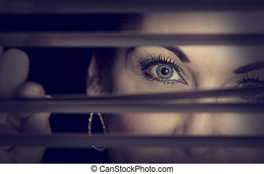 Portrait of a woman standing in darkness looking through blinds artistic conversion