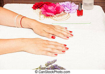 Hands of a woman with red nail polish posed by an...
