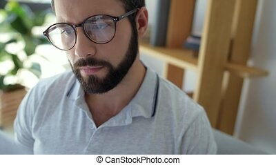Serious bearded guy looking through pile of documents