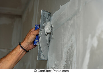 old manual worker with wall plastering tools renovating house